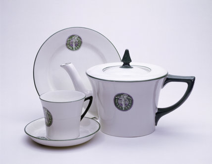 Photograph of white tea-pot, cup, saucer and plate, all with green and purple WSPU logo